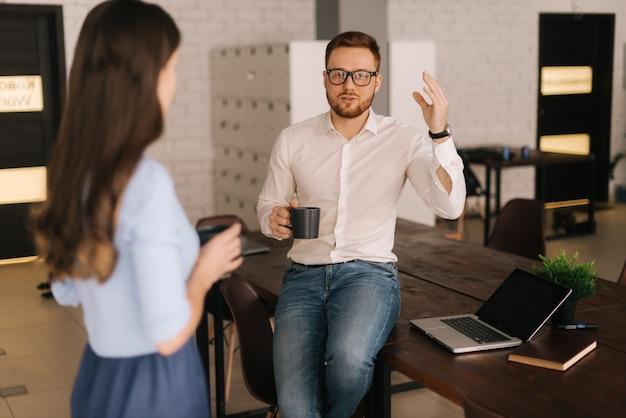 Funcionários homens e mulheres em pé com xícaras de café e conversando na sala do escritório