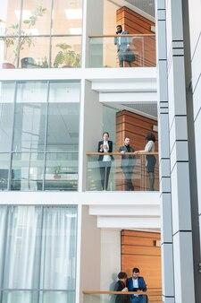 Funcionários jovens e multiétnicos modernos do centro de negócios, trabalhando uns com os outros em andares diferentes