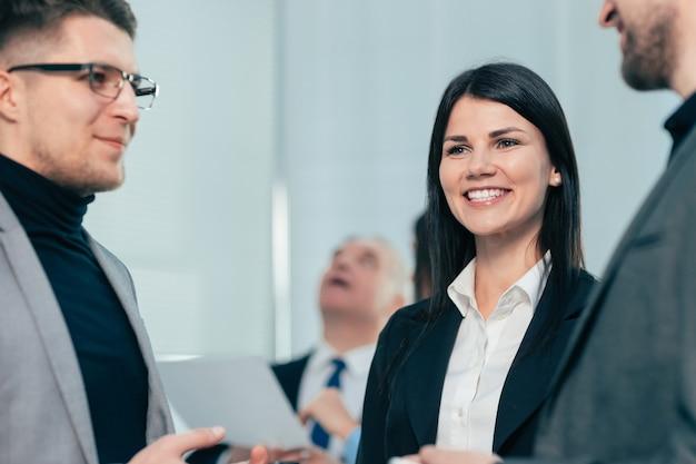 Funcionários jovens falam em pé no escritório. trabalho em equipe