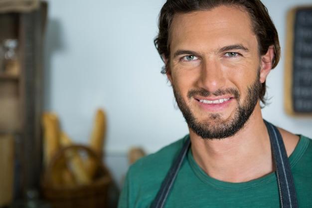 Funcionários masculinos sorridentes em pé na padaria