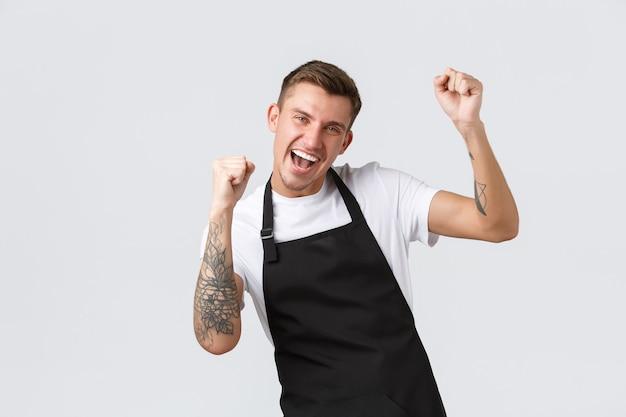 Funcionários, mercearias e conceito de cafeteria. garçom carismático feliz e amigável sorrindo, dançando alegremente, curtindo a abertura do café após o covid-19 lockdown, levantando as mãos e dizendo sim