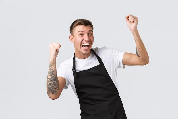 Funcionários, mercearias e conceito de cafeteria. trabalhador de mercearia alegre, barista de avental preto alegrando-se com as notícias maravilhosas, dizendo sim, ganhando, levantando as mãos em triunfo