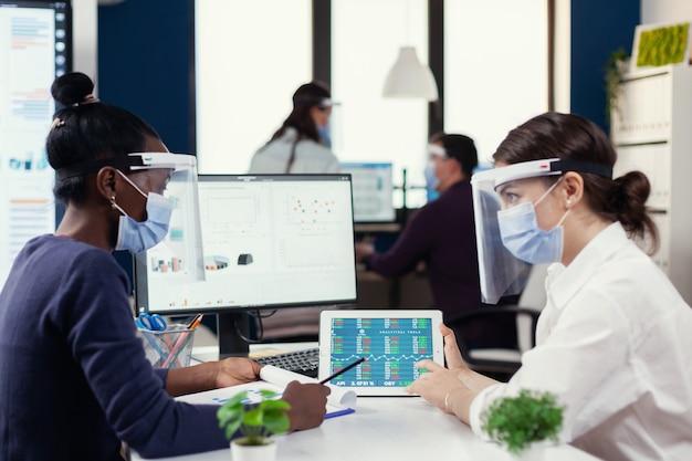 Funcionários multiétnicos com viseira e máscara de proteção sentados na mesa analisando dados financeiros. grupo diverso de empresários trabalhando e se comunicando em um escritório criativo com novo normal, r
