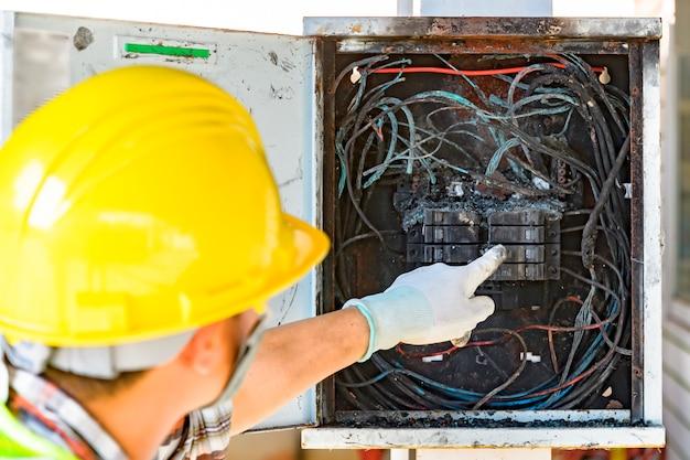Funcionários que verificam a causa da placa de circuito de controle de incêndio