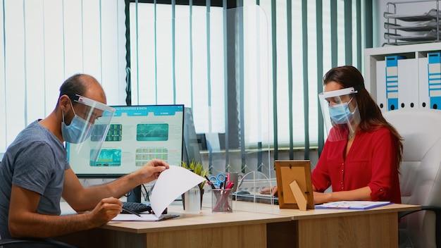 Funcionários usando máscara e viseira sentados na nova sala de escritório normal respeitando o distanciamento social. colegas de trabalho trabalhando em locais de trabalho modernos, respeitando as regras de proteção contra vírus covid usando plexiglass.