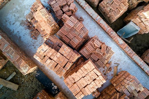 Fundação de concreto do porão ou primeiro andar da futura casa com pilhas de tijolos vermelhos para construção de paredes em dia ensolarado de verão, vista aérea.