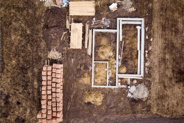 Fundação de concreto para o porão da futura casa, pilhas de tijolos e toras de madeira para construção em dia ensolarado de verão, vista aérea.