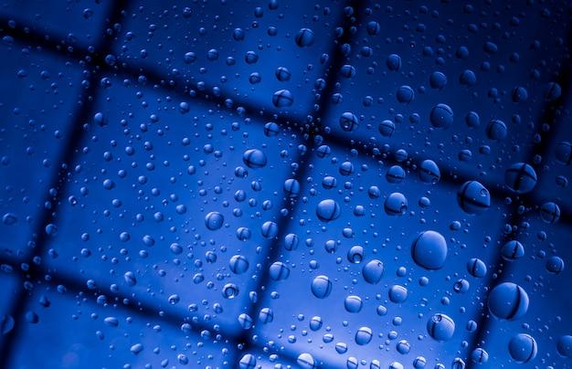 Fundo abstrato azul do borrão com gotas da água e reflexão no vidro transparente. fundo azul