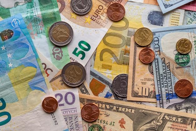 Fundo abstrato colorido feito de moedas diferentes do metal, de contas americanas, ucranianas e de notas de euro. dinheiro e finanças, conceito de investimento bem sucedido.