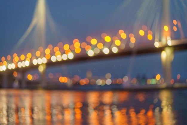 Fundo abstrato com bokeh luz dos faróis noturnos do carro da ponte. luzes noturnas da cidade grande