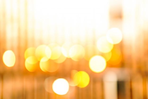 Fundo abstrato da luz amarela do bokeh do borrão.