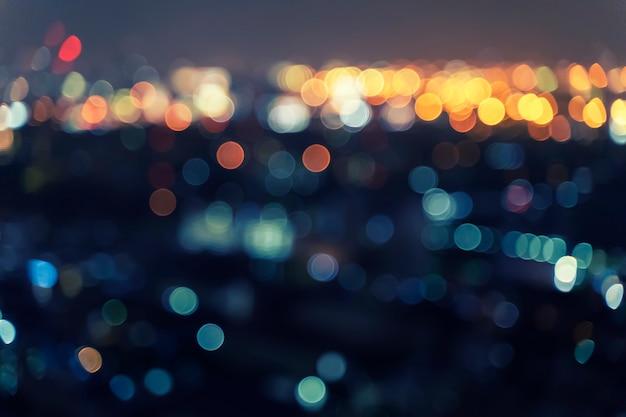 Fundo abstrato da luz borrada do bokeh na noite na cidade.