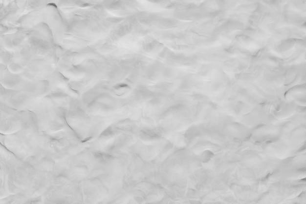 Fundo abstrato da textura branca da argila na parede. papel de parede de arte monocromático.