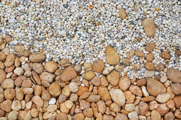 Fundo abstrato da textura do cascalho, teste padrão decorativo do assoalho de pedras do seixo.