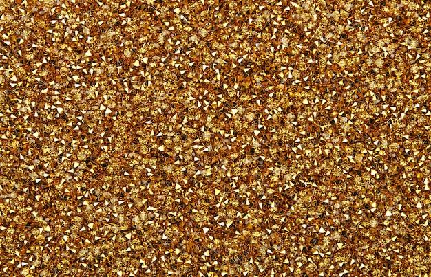 Fundo abstrato de cristais de strass coloridos de strass dourado brilhante, vista superior elevada, diretamente acima