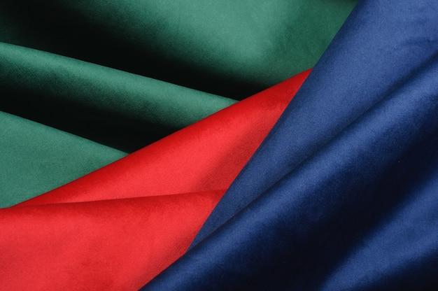 Fundo abstrato de dobras geométricas de tecido de veludo vermelho e verde azul. textura de tecido de veludo luxuoso