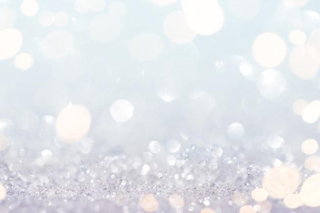 Fundo abstrato de neve e glitter com luzes douradas