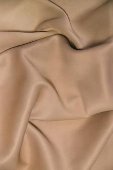 Fundo abstrato de tecido de luxo. dobras em ondas de tecido de seda. a textura do material acetinado. plano de fundo de natal ou elegante design de papel de parede. tecido bege, cores naturais.