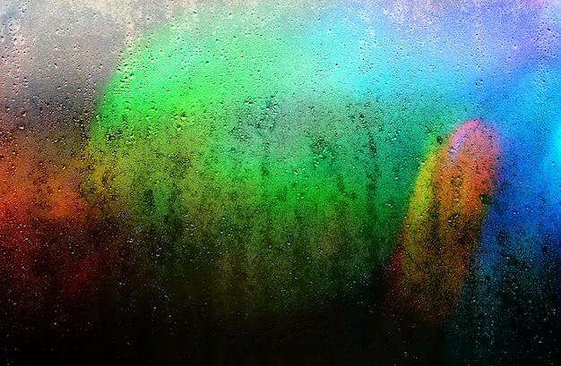 Fundo abstrato de um vidro chuvoso com cores impressionantes e espaço da cópia.