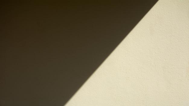 Fundo abstrato de uma parede amarela pálida com sombras da janela.