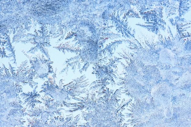 Fundo abstrato do gelo, fundo azul com rachaduras na superfície do gelo. copie o espaço, textura natural, macro. padrão de gelo no vidro da janela de inverno