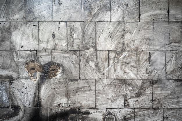 Fundo abstrato do grunge. ladrilhos sujos na parede com vestígios borrados de fuligem e poeira. cinzento