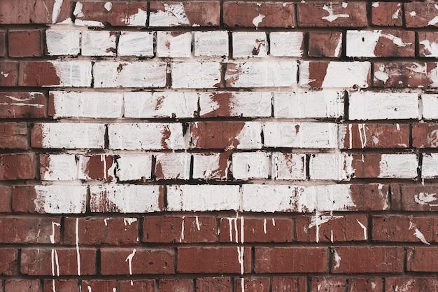 Fundo abstrato do grunge. parede de tijolo velha manchada com tinta. tinta branca com manchas em tijolo vermelho.