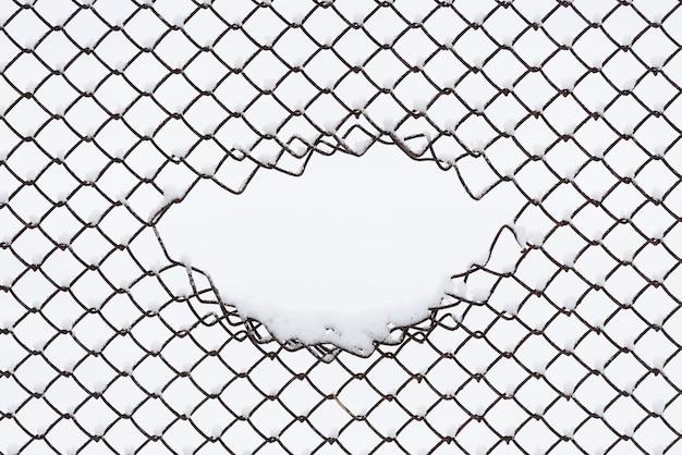 Fundo abstrato do inverno com espaço da cópia. padrão geométrico de cerca de arame na neve