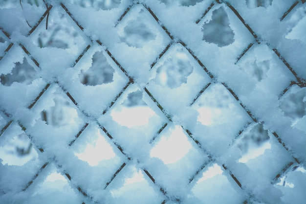 Fundo abstrato do inverno. neve na grade de metal