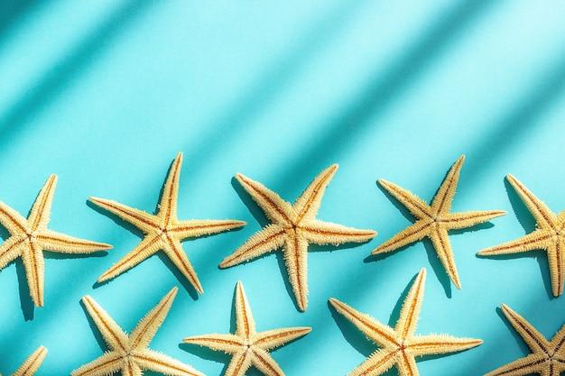 Fundo abstrato do mar marinho. fundo de turquesa com estrelas do mar, luz e sombra duras.