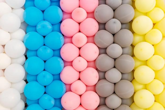 Fundo abstrato do teste padrão de balões coloridos misturados decorados na parede.