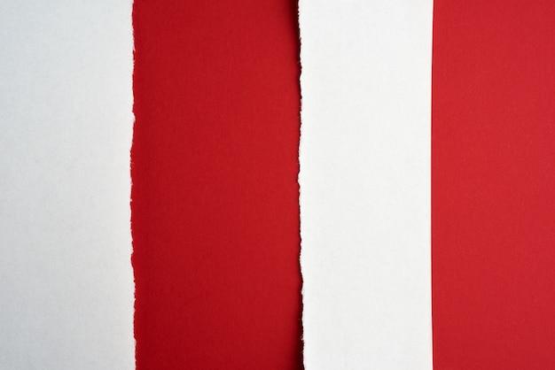 Fundo abstrato vermelho com listras de papel branco rasgado, close-up
