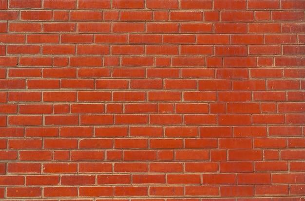 Fundo alaranjado da textura da parede de tijolo. plano de fundo para o texto. conceito de arquitetura exterior.
