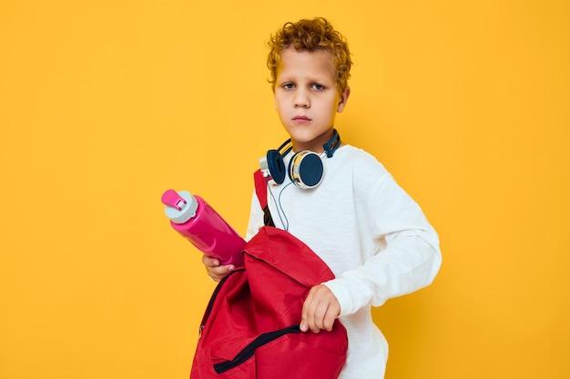 Fundo amarelo adolescente com garrafa de água para entretenimento com fone de ouvido