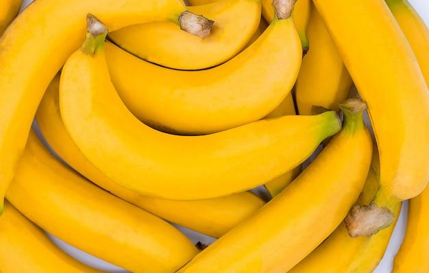 Fundo amarelo banana fresca, close de um pacote de bananas