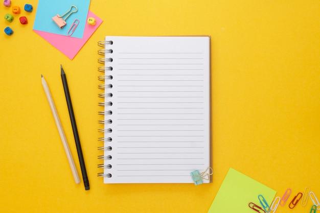 Fundo amarelo com caderno e material escolar