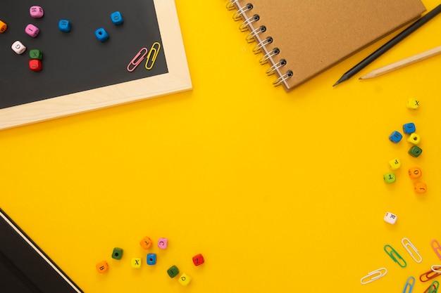 Fundo amarelo com cadernos e material escolar