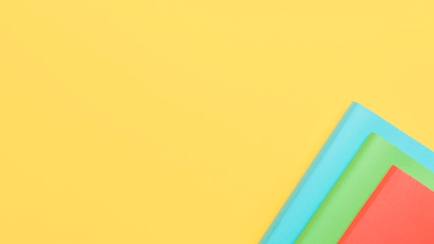 Fundo amarelo com folhas de papel no canto