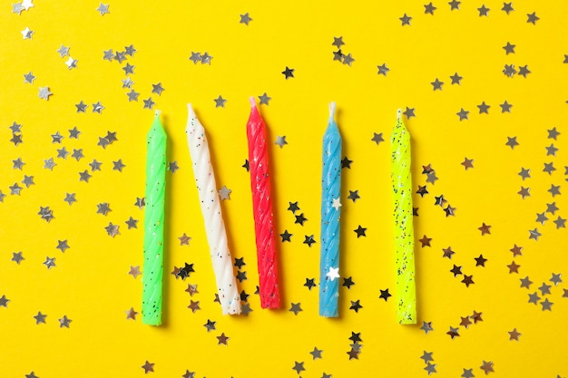 Fundo amarelo com velas de aniversário e glitter, espaço para texto