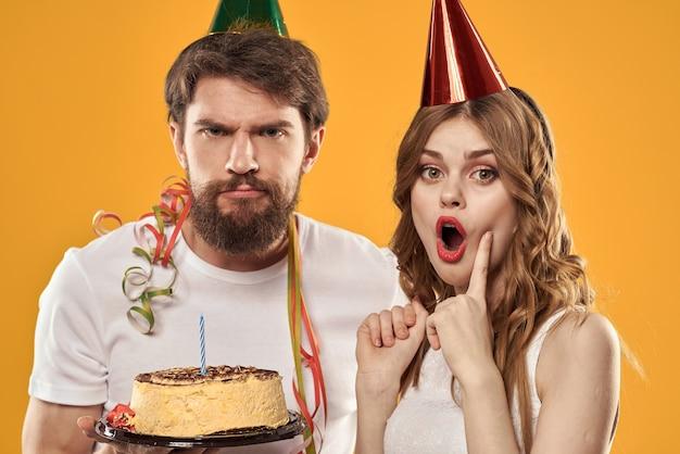 Fundo amarelo de bolo festivo de aniversário de homem e mulher