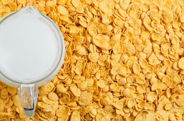 Fundo amarelo de flocos de milho. leite em uma jarra. café da manhã saudável e nutritivo. copie o espaço