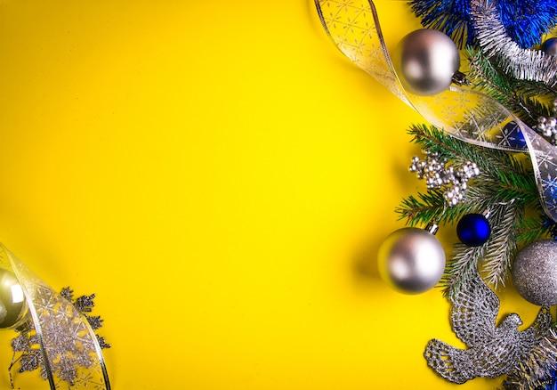 Fundo amarelo de natal decorado com abeto e brinquedos