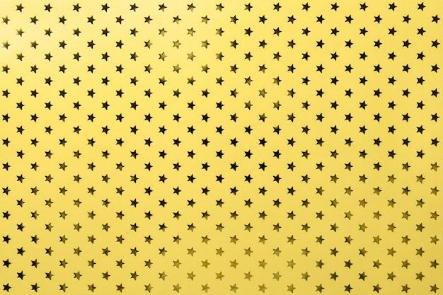 Fundo amarelo de papel de folha de metal com um padrão de estrelas douradas