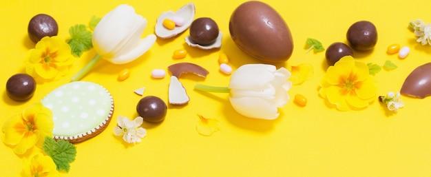 Fundo amarelo de páscoa com ovos de chocolate, doces e spri
