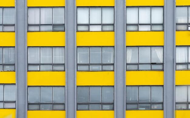 Fundo amarelo e cinza do edifício com janelas. exterior de arquitetura.