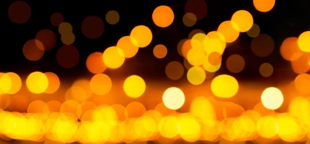 Fundo amarelo ouro bokeh feliz ano novo 2022. efeito abstrato luz noite fora do papel de parede do círculo de foco. para férias de celebração de festa de natal ou conceito de fundo de tecnologia.