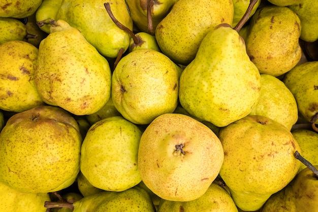 Fundo amarelo pêra. variedade de peras frescas cultivada na loja. pêra adequada para suco, strudel, purê de pêra, compota