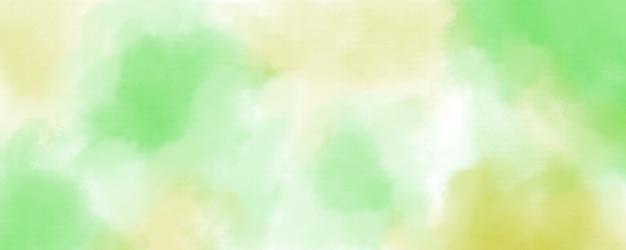 Fundo aquarela em cores verdes e amarelas, respingos em tons pastéis suaves e manchas com sangramento de franjas pintando em formas abstratas de nuvens com papel