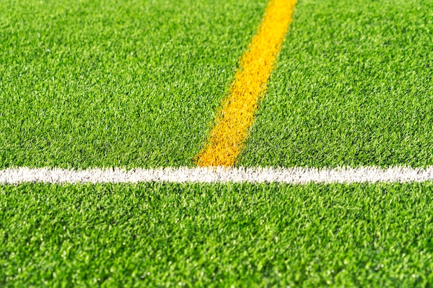 Fundo artificial verde do campo de futebol do futebol do relvado da grama com limite branco e amarelo da linha. vista do topo