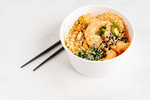 Fundo asiático do alimento com o picante puxão do camarão com arroz, algas e sementes de gergelim, abacate em uma lancheira com os chopsticks no branco. almoço de frutos do mar saudável. faça dieta alimentar. vista superior com espaço de cópia.